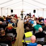 Friluftsgudstjenesten måtte holdes i telt siden været ikke viste seg fra sin beste side. Foto: Robin Lund, fotonaut.no